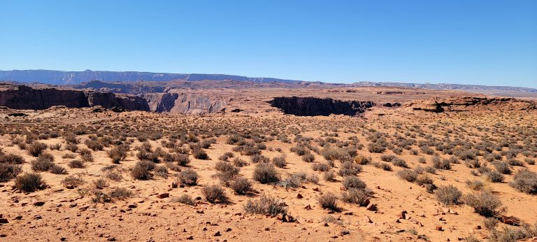 The view of the desert scrub brush leading up to the horseshoe bend where the giant hole is barely visible.