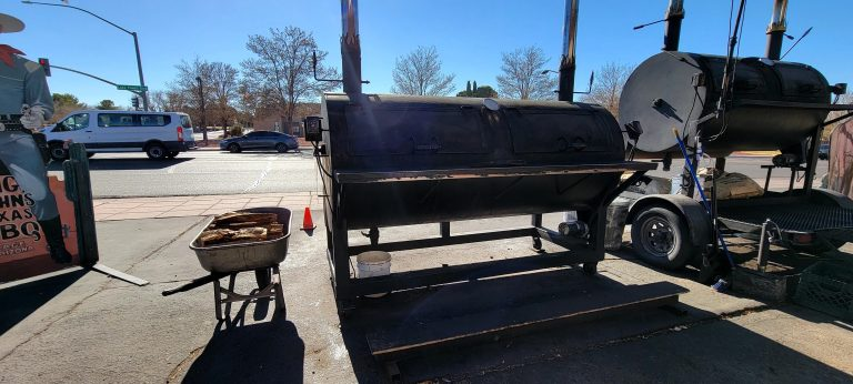 A huge steel smoker sitting in the parking lot at Big John's Texas Barbecue with a wheel barrow of wood next to it.