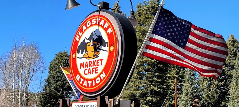 The sign for the Flagstaff Station Market Cafe. It is one of the classic old circular signs of a gas station but redone with a modern logo.