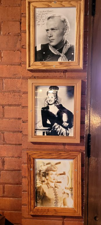 A wall full of photos including Lucille ball at the El Rancho hotel.