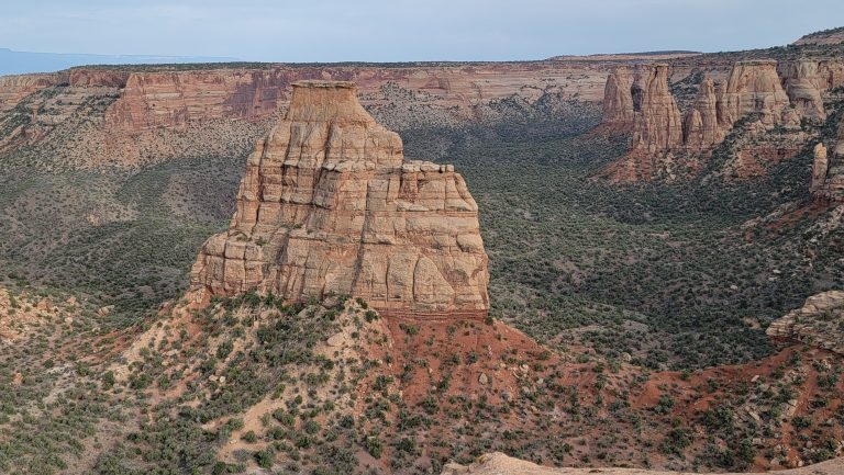 A view of a giant triangle shaped rock formation from the side of Otto's Trail.  The rock stands up from the middle of the canyon floor.