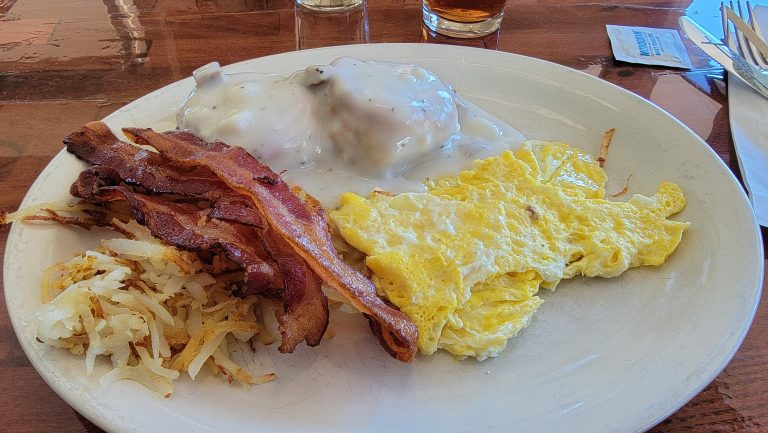 The biscuit and gravy breakfast from Canyon Steak and Waffle House.  The breakfast had two biscuits and gravy  with eggs on the side.  A pile of hashbrowns next to the eggs and the bacon on top of the hashbrowns.