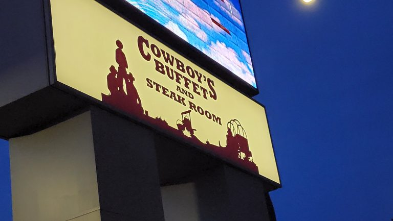 The sign for Cowboy's Buffet and Steak Room under the video board marquee for Ruby's Inn.