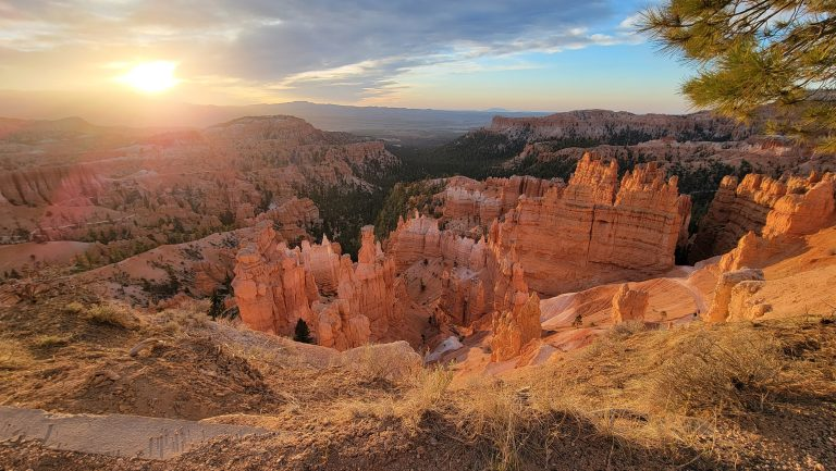 The Hoodoo's glowing during sunrise at Bryce Canyon.  They have taken on an orange tint in the towering rocks.  The sun has just cleared the mountains in the background and the rocks are beginning to glow.