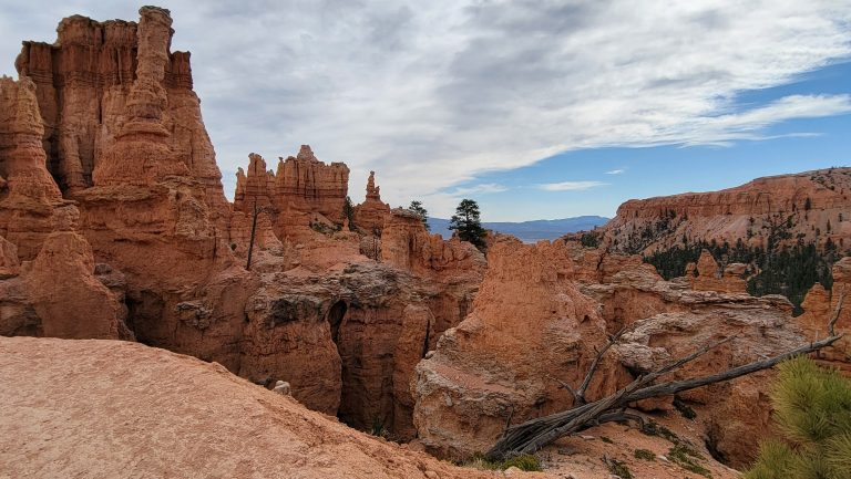 A series of spires to the left and rock walls in the background of this pictures looking down the canyon towards the mountains on the Peek-a-Boo loop in Bryce Canyon.
