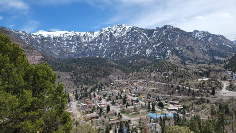 From the Ouray Perimeter Trail the town of Ouray in the bottom of the photo at the base of a range of snow capped mountains