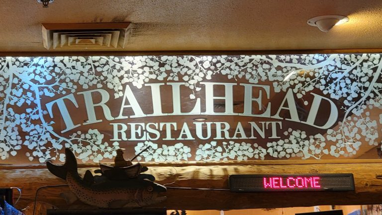 An Old fashioned sign for Trailhead Restaurant inside of the building.