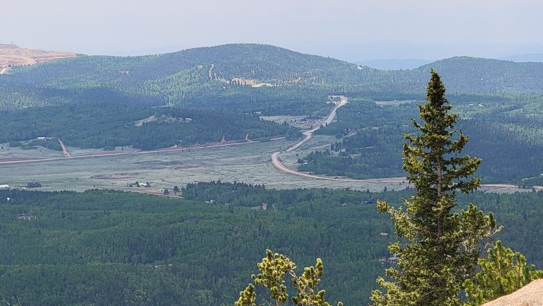 The view to the Southwest shows US67 cutting through a valley of trees with some tree covered hills in the distance from the top of the Pancake Rocks and Horsethief Falls hike.