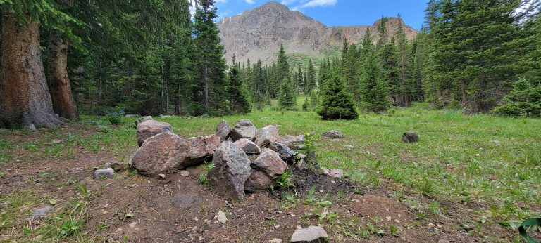 As you approach the end of the Grizzly Gulch hike there is an abandoned fire pit of stone in the foreground and perfectly clear Grizzly Peak in the background.