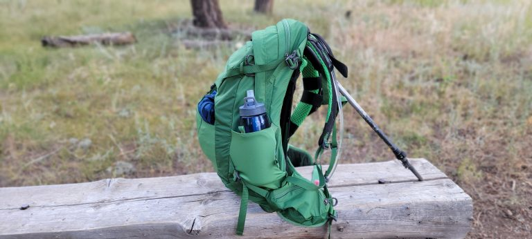 The side view of the Osprey Manta 24 backpack reveals side pieces that wrap around the hips on either side that have pockets in them.
