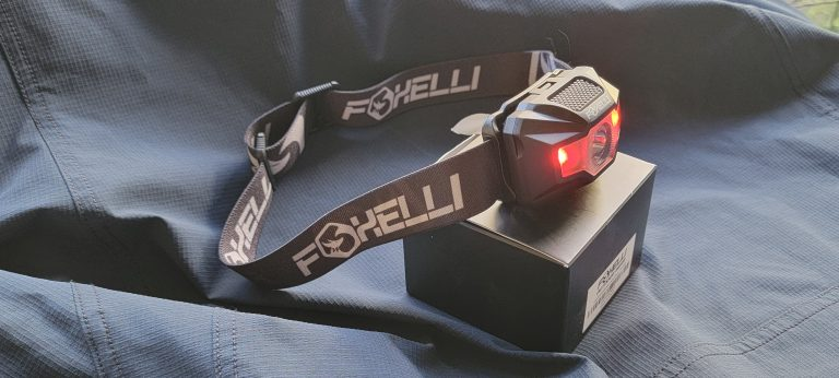 The Foxelli MX200 headlamp on display with the two outer red lights activated.  The small light has the headband coming from behind to see the flexibility.