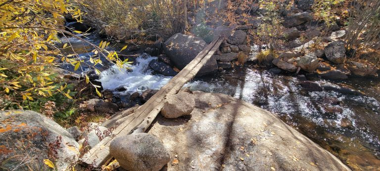 Two very thin and narrow pieces of wood stretch across a gap at the creek on the Abyss trail to Helms Lake