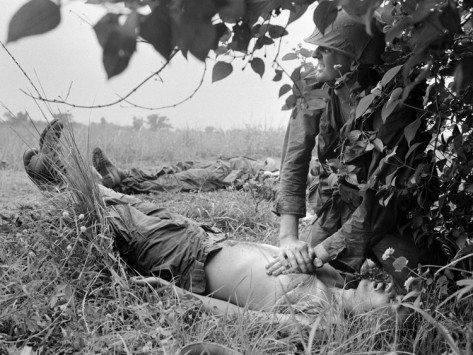 Um soldado tenta reanimar um companheiro.