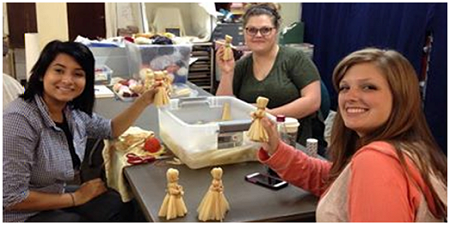 Faulkner County Museum interns work on corn husk dolls