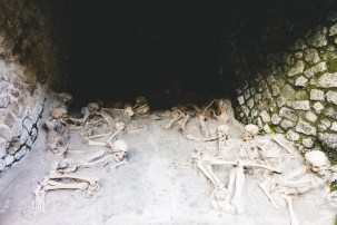 Skeletons (copies of) as found in the boat houses. These people, waiting for rescue by the sea, died instantly from the intense heat from the ashes (500 degrees Celsius)