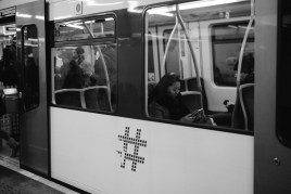 The hastag is the symbol of the metro system. Here's a girl, most likely interacting with social media, on thr train.