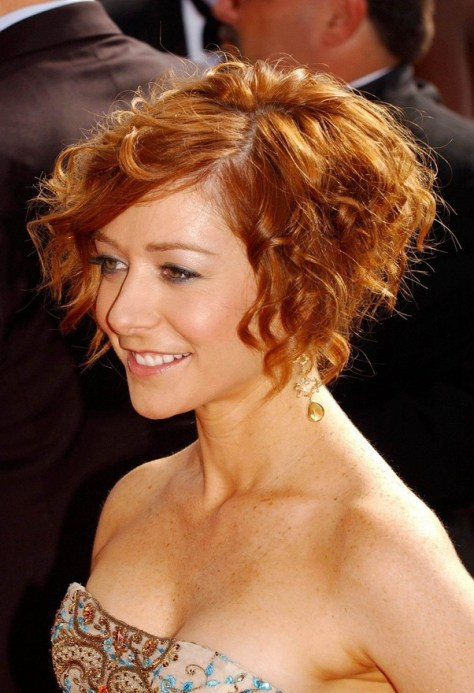 Medium bob cut styled with thick curls and waves for motion.