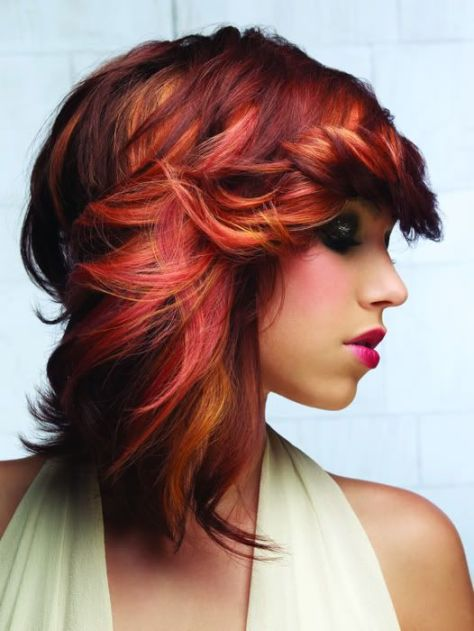 Rockstar like hairstyle with thick layers and an extended neckline.