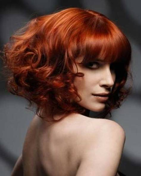 Red hair with curls cut at shoulder length and styled to the back.