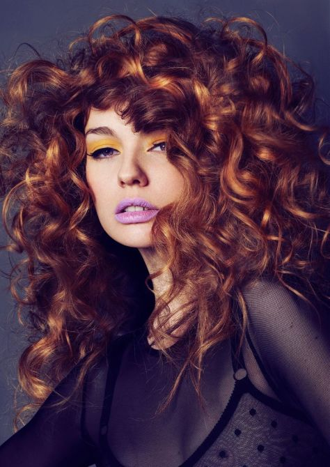 Redhead with large curls that frame her face.