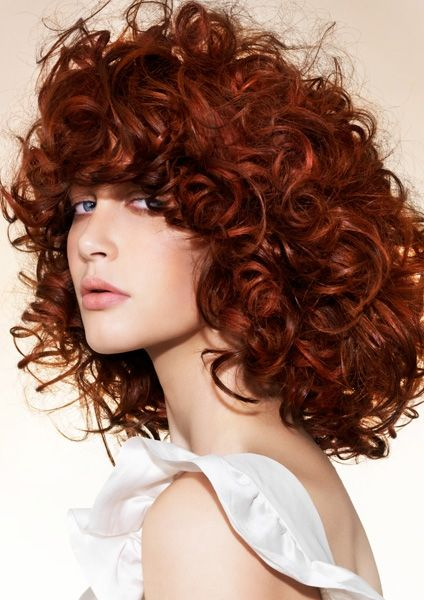 Redhead curls with hair nestled around the shoulders.
