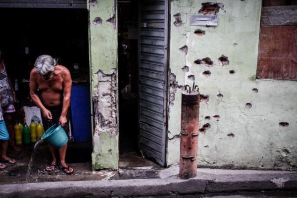 Parede de casa perfurada por tiros no Complexo do Alemão. Bento Fábio / Coletivo Papo Reto