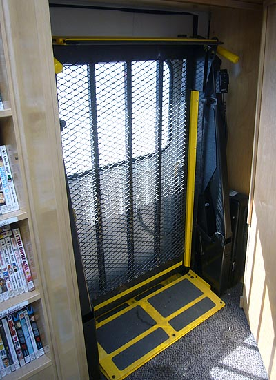 Corrugated metal wheelchair lift, with yellow safety edges, sits folded upright inside wall recess