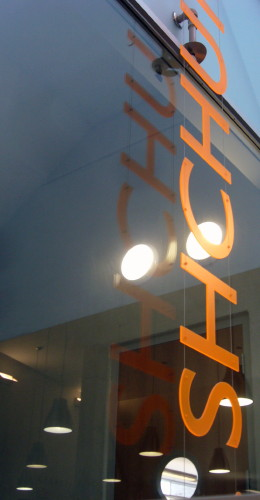 Peach-coloured Gill letters read SHCHU and hover on top of a window