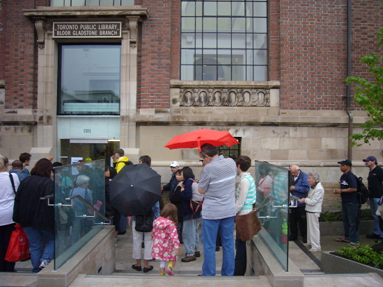 People, many carrying umbrellas, wait outside a brick building with an old sign reading TORONTO PUBLIC LIBRARY BLOOR GLADSTONE BRANCH