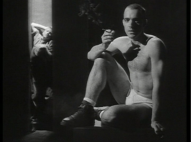 Man in underwear sits on pedestal smoking a cigarette, while another man seems crammed into a closet-like illuminated space well behind him