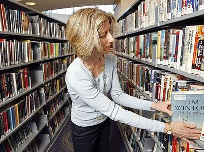 Jane Pyper pulls a Tim Winton book off a shelf, or slides it into that same shelf