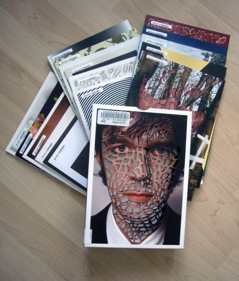 Booklets arranged under box, with cover perforations arranged across Sagmeister's face