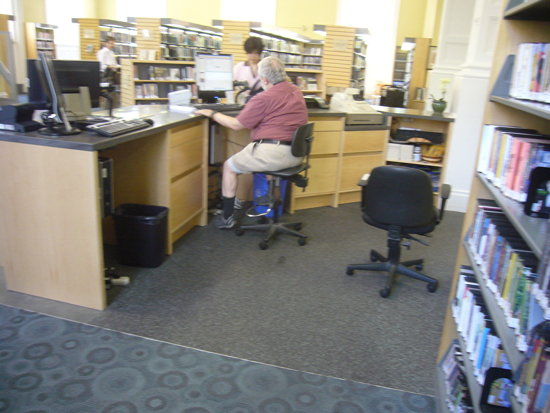 Man perches on stool behind desk, with nowhere to fit his legs under below-desk computer