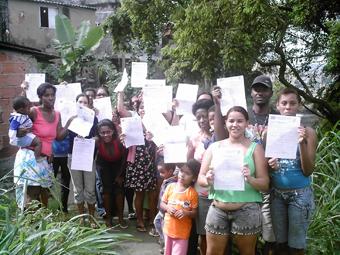 Com a chegada da reportagem, moradores da Rua Luis Vargas, na Morro do Urubu, zona norte do Rio, buscaram o documento de interdição de suas casas. Foto: Eduardo Sá/Fazendo Media.