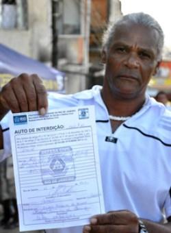 Morador do Morro dos Prazeres com o auto de interdição da prefeitura, que segundo alguns relatos em sua maioria não está sendo articulado por meio da Associação de Moradores local. Foto: Fabio Pereira.