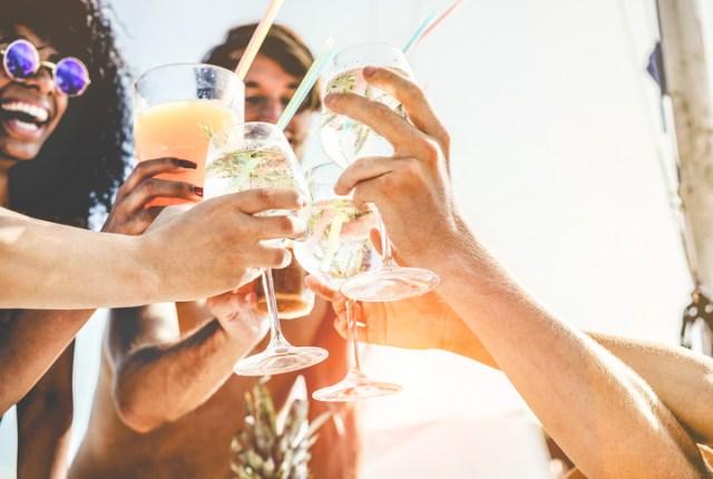 amigos rindo na praia com bebidas