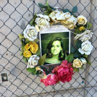 Floral display affixed to chain link fence outside the memorial featuring a victim of the bombing named Jeanne Welch.