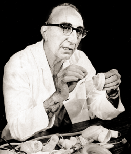 January 5, 1971 - Famed artificial heart surgeon Dr. Michael DeBakey explains new advances in the development of artificial hearts. DeBakey, holding a part of the latest artificial heart, said although development is advancing with experimental animals he could not say when the heart could be used successfully in humans. Other parts on the table represent ten years of research in artificial hearts.