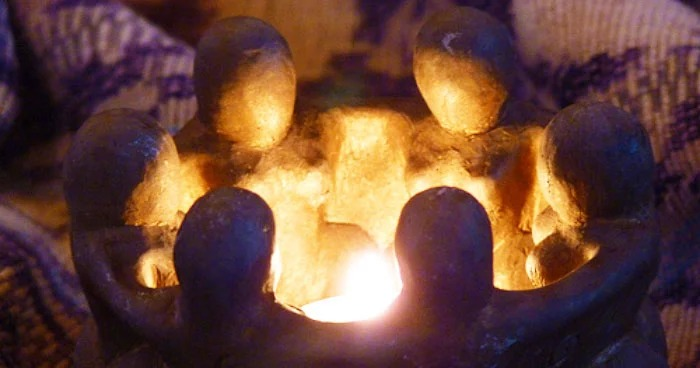 A candle holder formed by six figures with their arms around each other, surrounding a flame in the center.