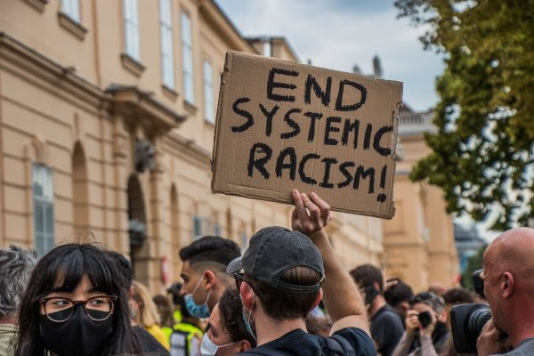 """A white person in a baseball cap and a mask holds up a cardboard sign that reads, """"End Systemic Racism!"""" at a protest. Image via Pixabay."""