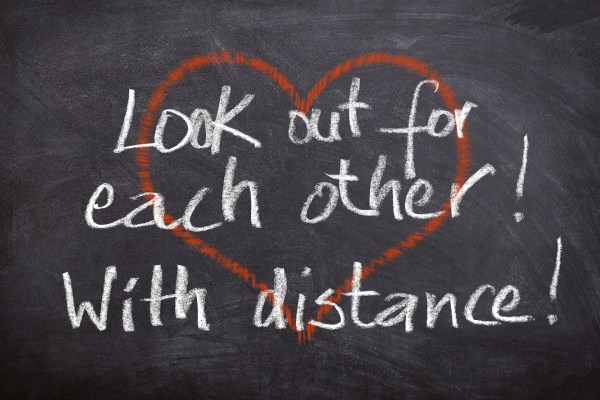 "Over top of a red outline of a heart are the words, ""Look out for each other! With distance!"" written in white chalk."