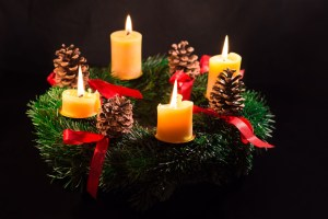A green evergreen Advent wreath, adorned with red ribbons, four pinecones, and four lit pillar candles.
