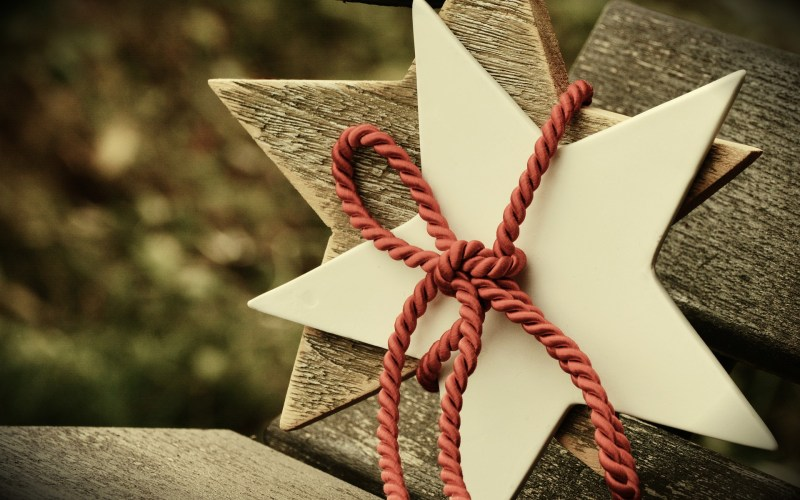 A white ceramic five-pointed star is stied over a wooden five-pointed star with a thick red cord.