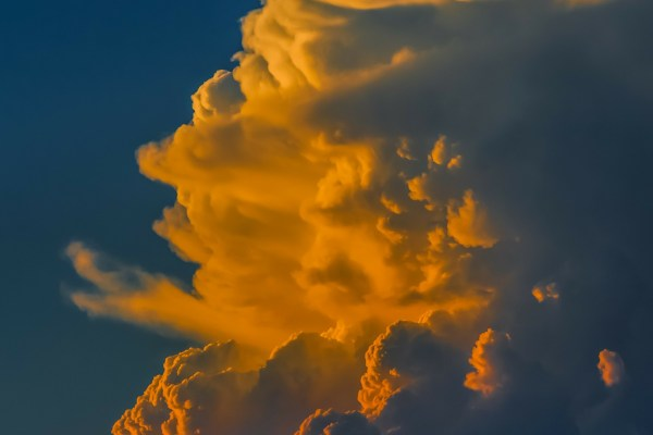 A towering white cloud is lit up in various hues of orange and yellow by the setting sun.