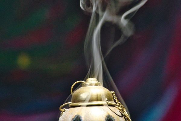 The smoke of incense wafts out from various openings in a golden censer. Image via Pixabay.