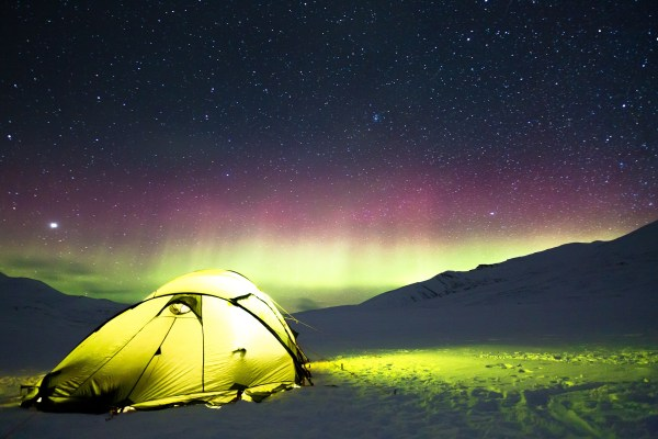 A yellow tent is lit from the inside on a snowy tundra, while vivid green and red auroras light up the night sky along the horizon. Image by Noel Bauza from Pixabay.