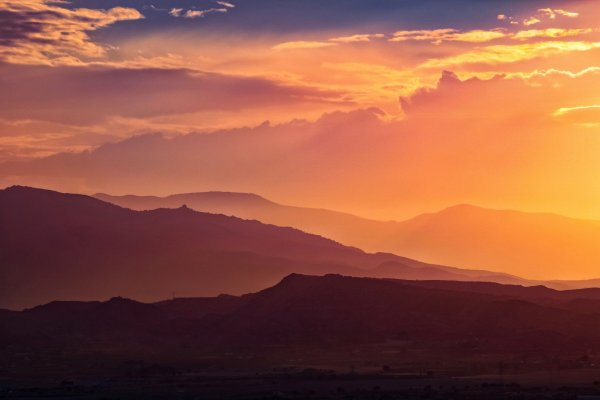 A mountain vista at sunset. The slopes of the mountains appear in various shades of purple, while the sky is lit up with blue, orange, and gold. Fog drifts in layers across the landscape. Image via Pixabay.