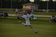 Junior Landon Campbell kicks the ball before it goes out of play.