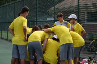 The tennis team huddles together to get some pre-game motivation before the match.