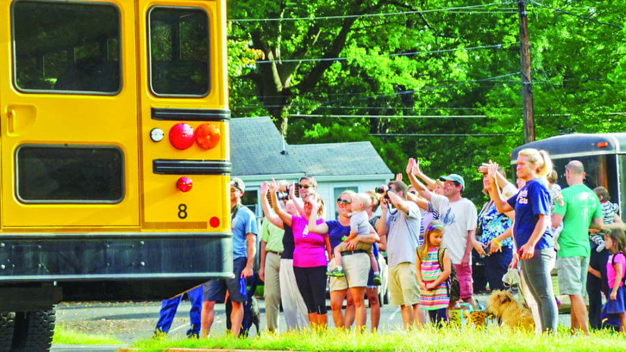 FALLS CHURCH FAMILIES WAVE GOODBYE to their students on the first day of school in 2014. The Predictable Ryde app aims to allow parents to know when their child's bus is arriving. (Photo: Courtesy of John Wesley Brett/FCCPS Photo)